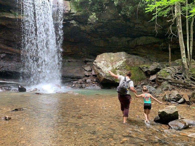mother and daughter balance on rocks near waterfall in Ohiopyle State Park, photo from a camper on The Dyrt