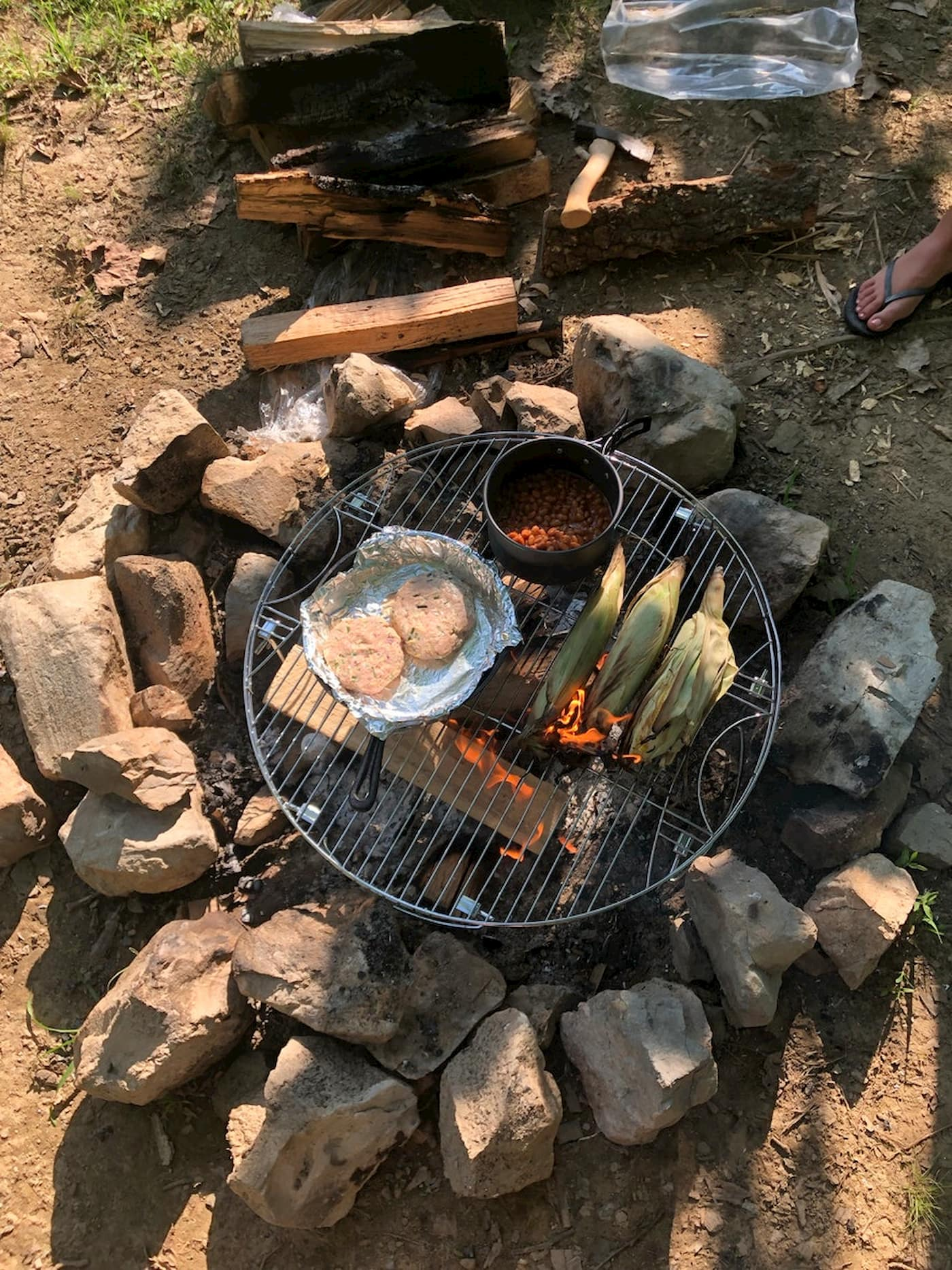 Corn, burgers and beans cooking over a fire pit.