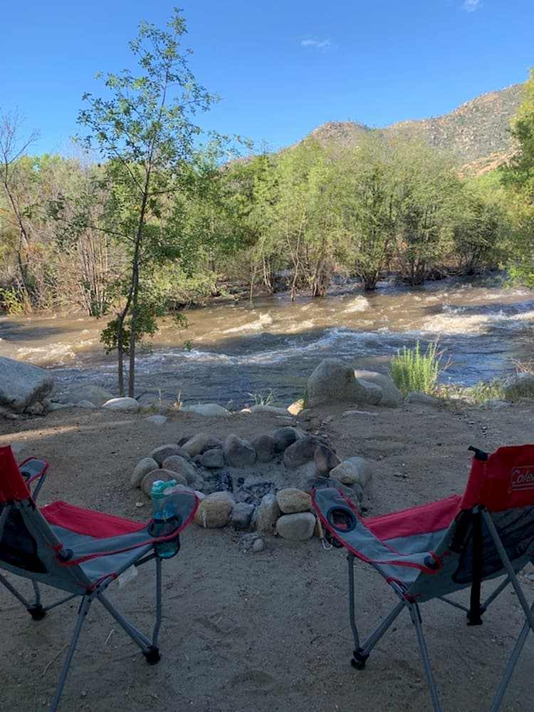 a campsite with chairs and a fire pit near a flowing river