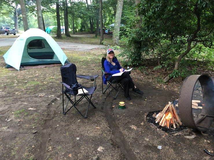 female camper sits between campfire and tent at Rocky Neck State Park, photo from a camper on The Dyrt