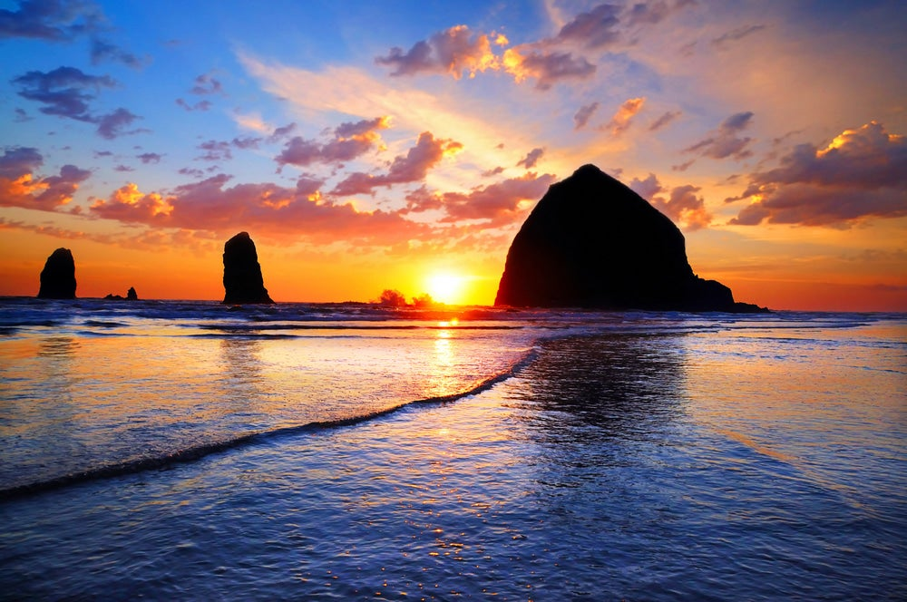 Haystack rock at beach with sunset in background