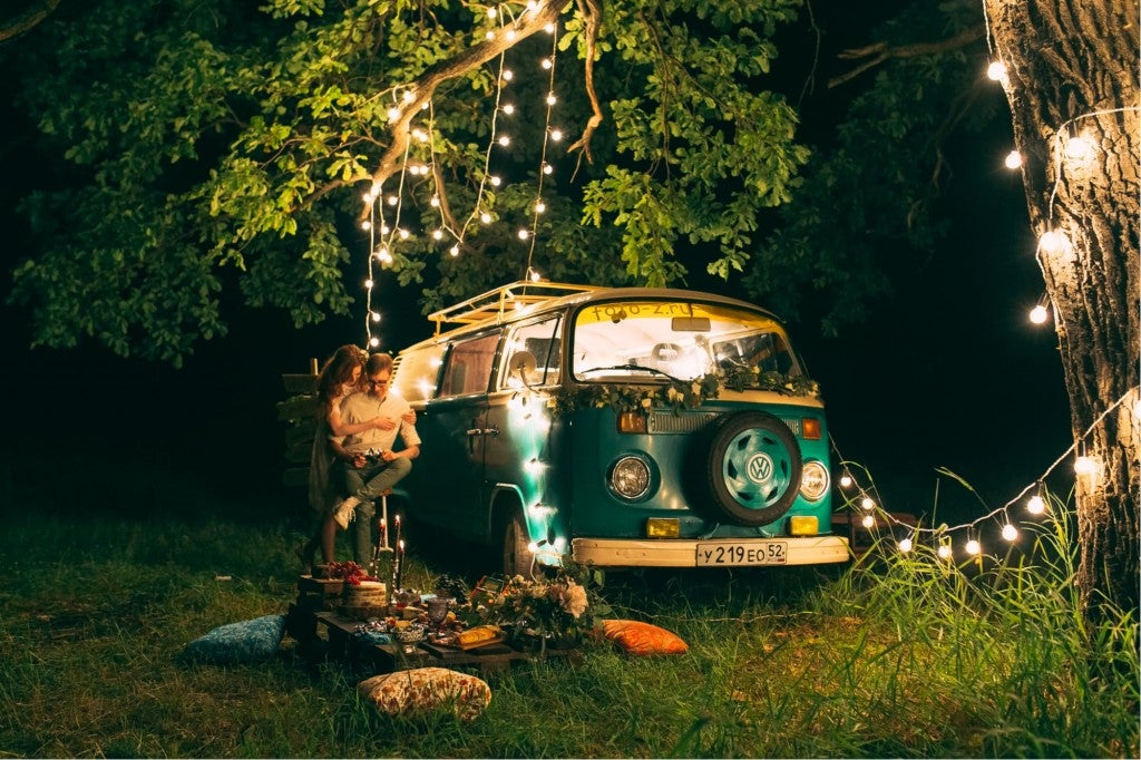 a couple in the woods next to an old van