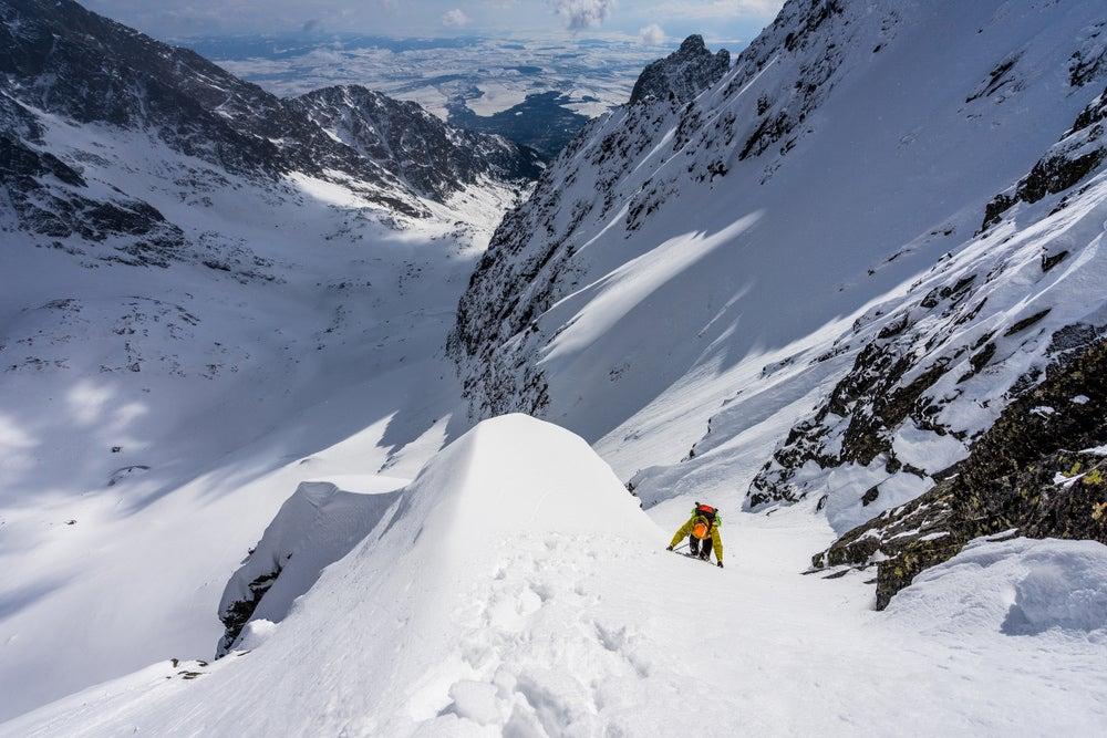 a man climbing a snow bank on a mountain in france