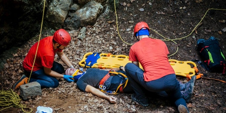 Search and rescue alpinists setting up an immobile person on a stretcher.