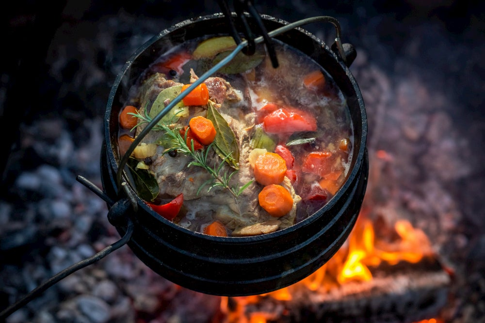 Hunter's stew in cast iron over a fire.