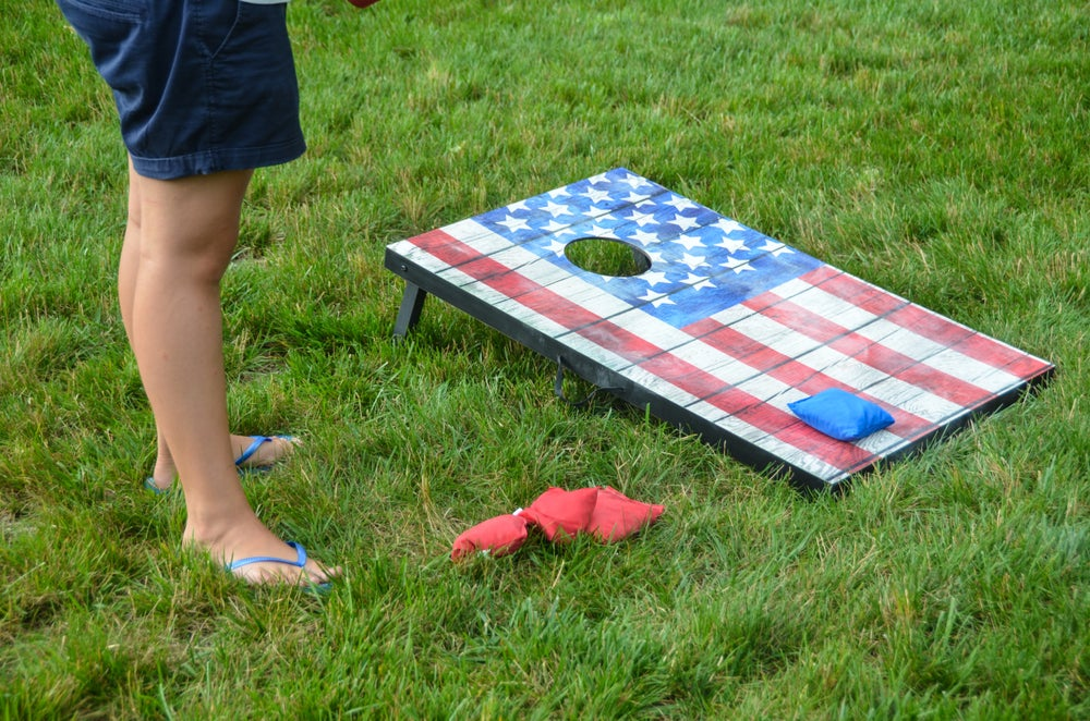 Person playing corn hole.