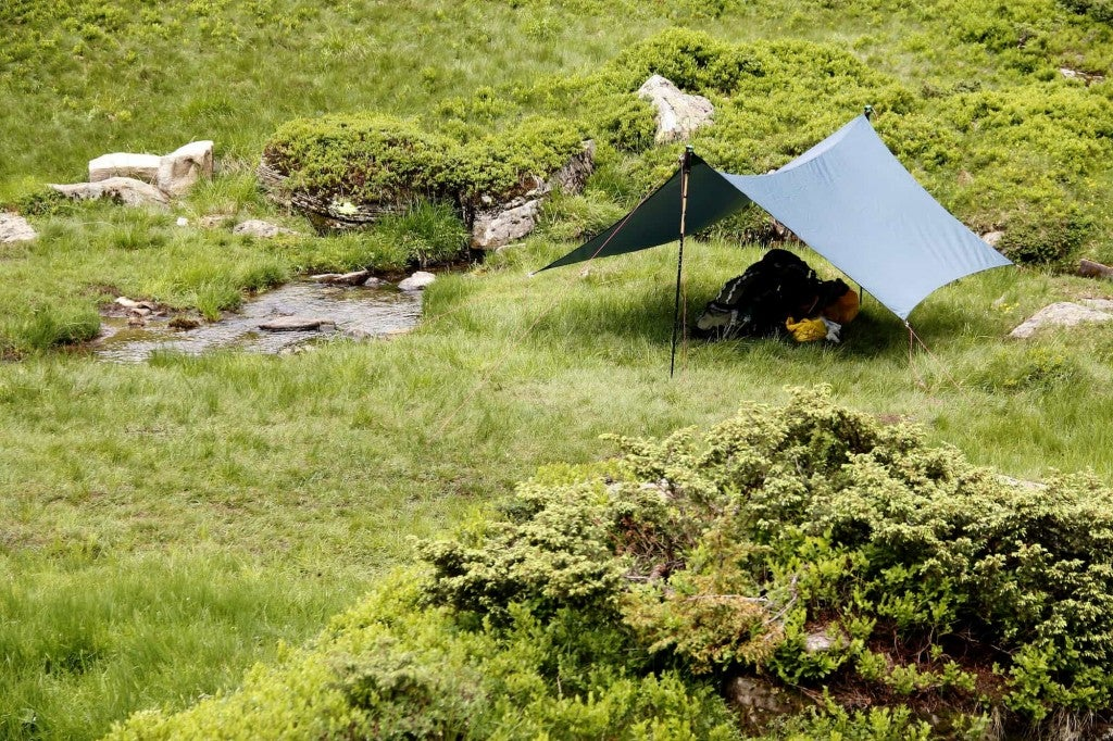 Backpackers tarp camp setup beside a creek.