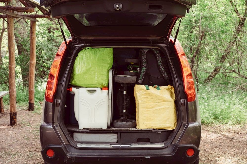 Car packed up with camping gear and a water jug.