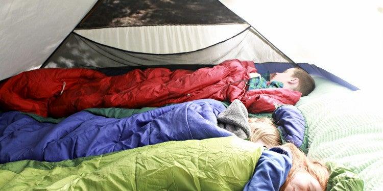 Three kids sleeping in a tent.