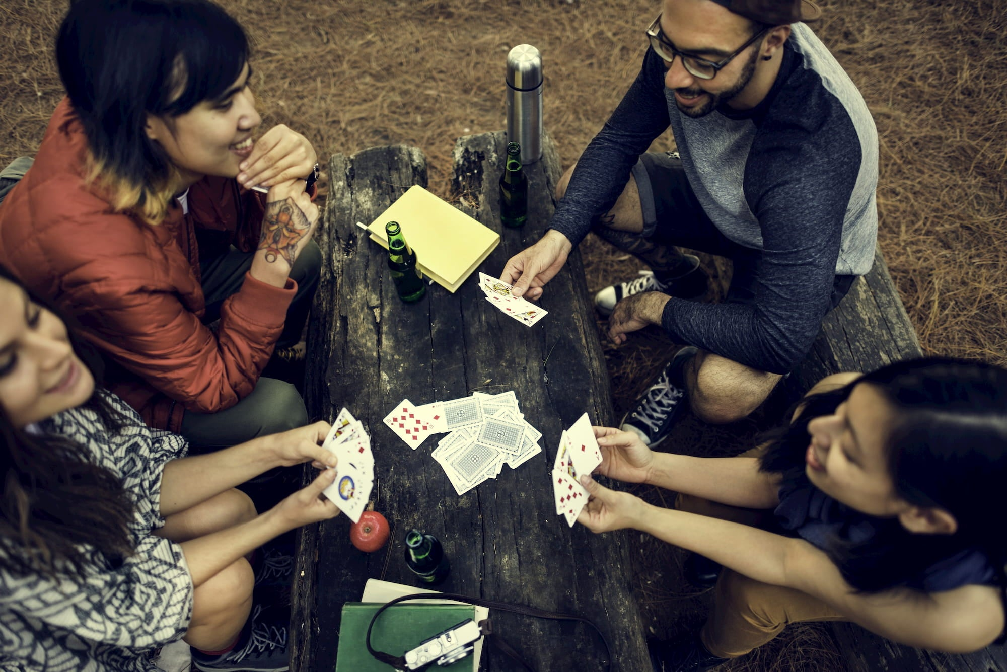 Friends playing cards a round a picnic table.
