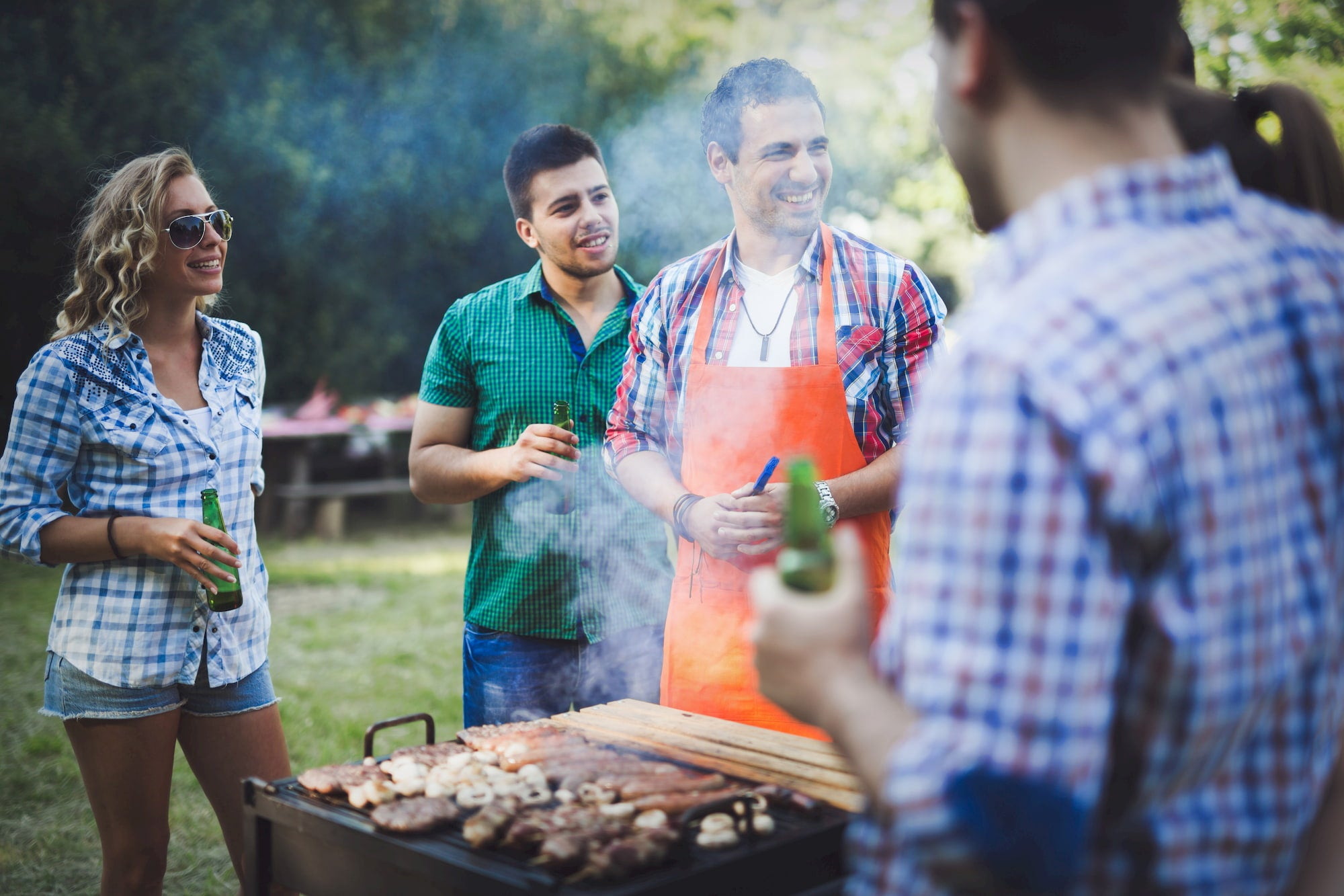 Friends around barbecue laughing