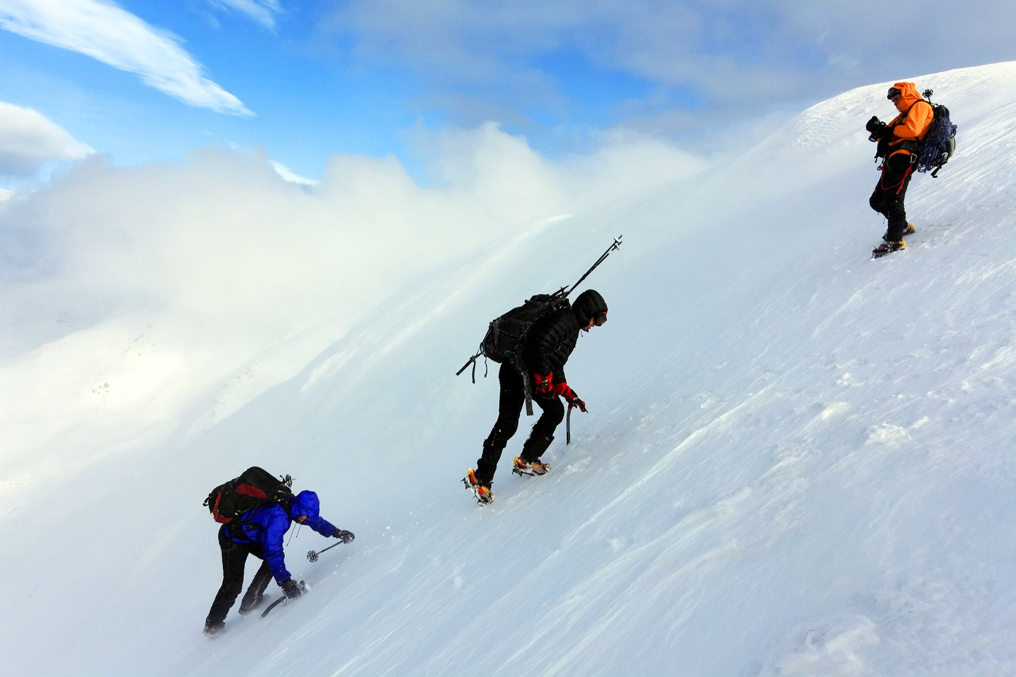 three climbers ascent a snow bank while alpine climbing