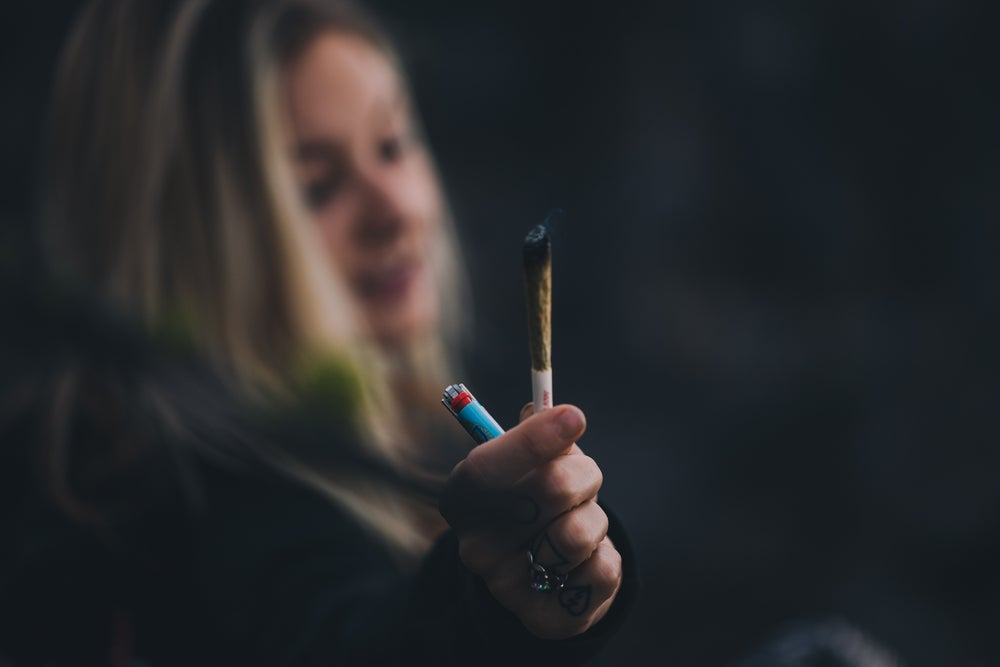 a woman holding a joint and a lighter