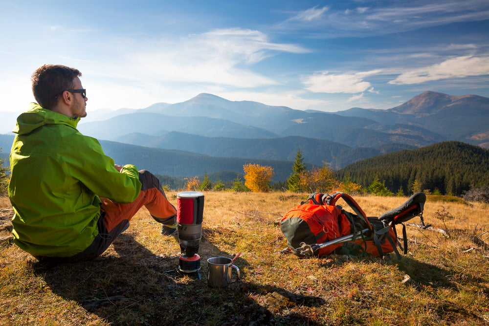 Backpacker using compact stove camping cooking gear on the trail.
