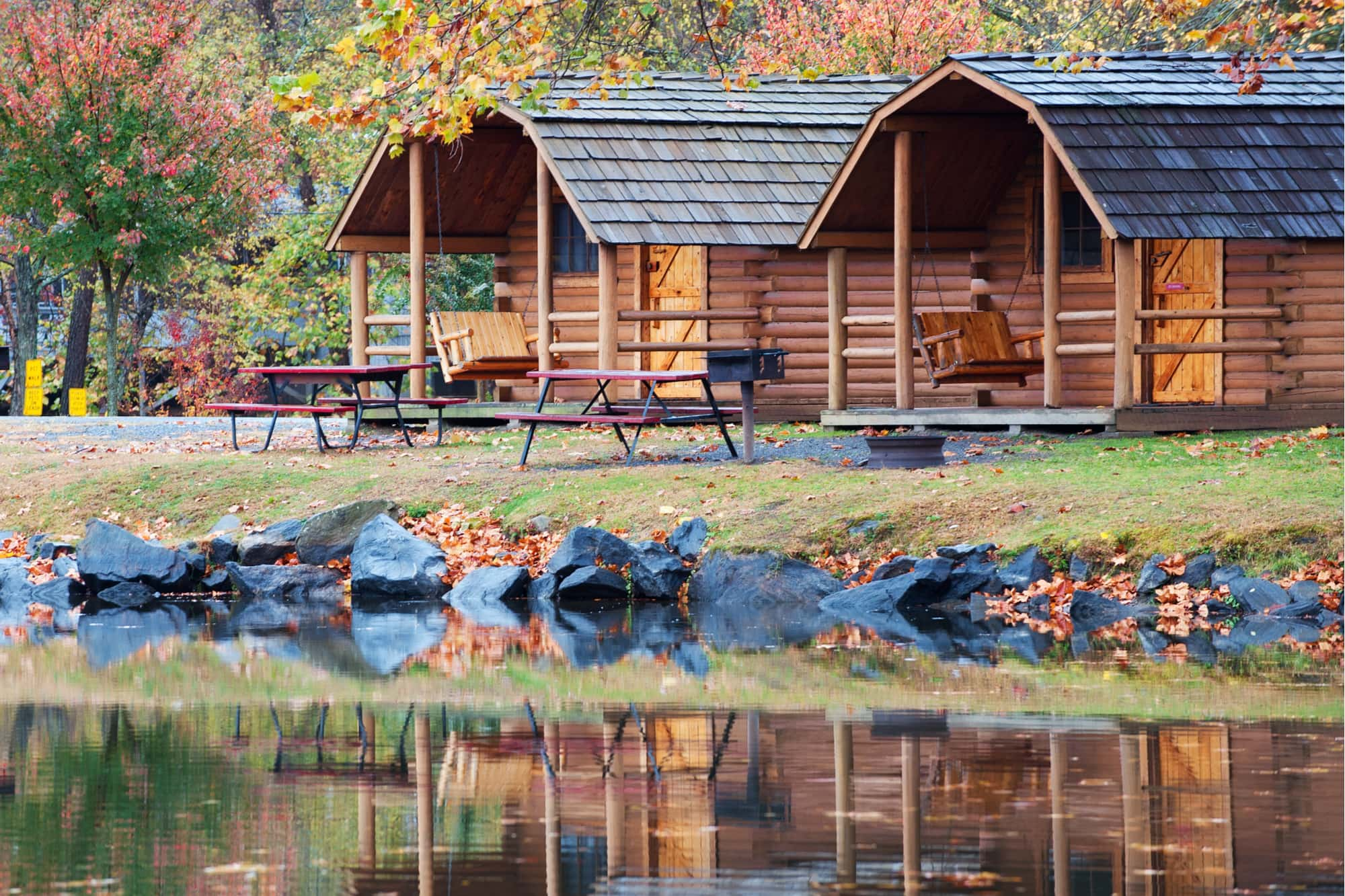 Fall colors on trees and a cabin reflecting in the water of a small lake in North Carolina