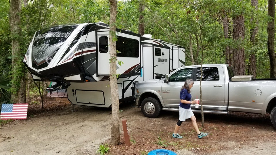 woman crosses in front of her large RV campsite in Myrtle Beach State Park, photo from a camper on The Dyrt