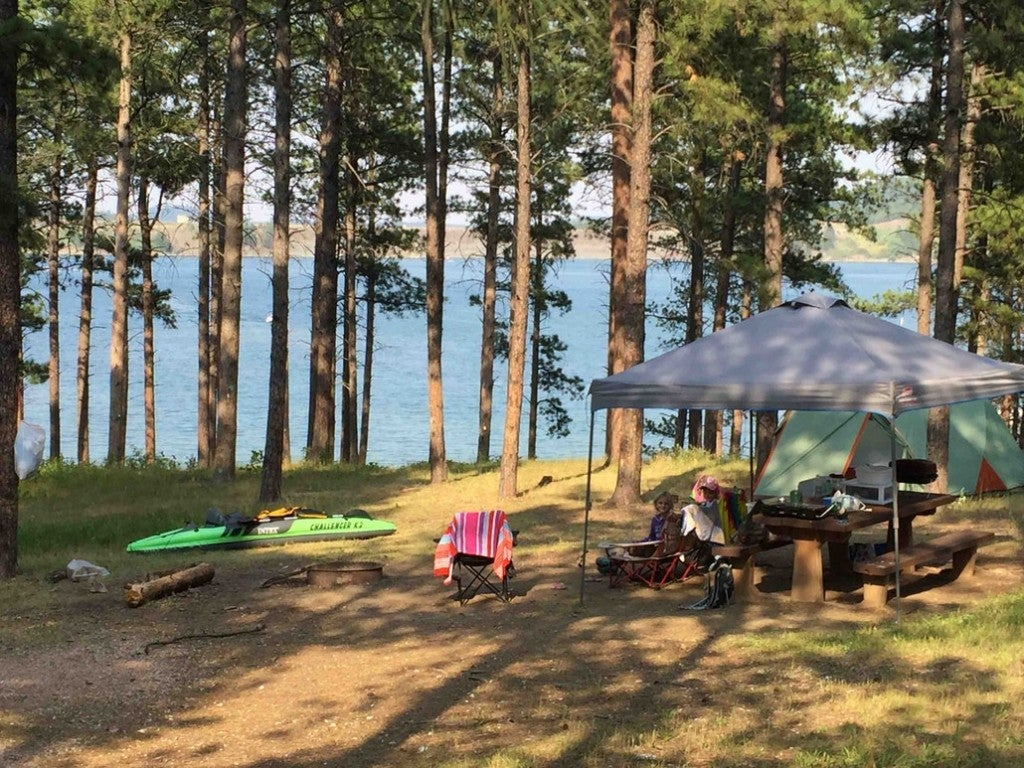 a campsite on the shores of a lake with a car, tent, table and kayak