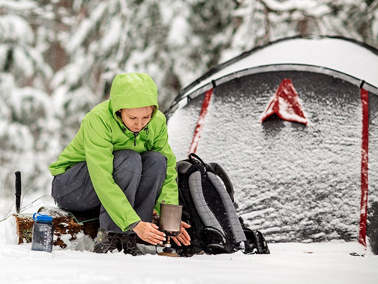 woman survival camping in winter snow