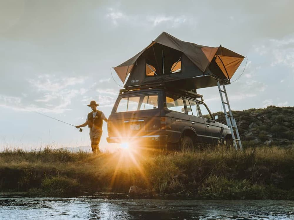 Tent on top of car with man walking toward lake to go fishing
