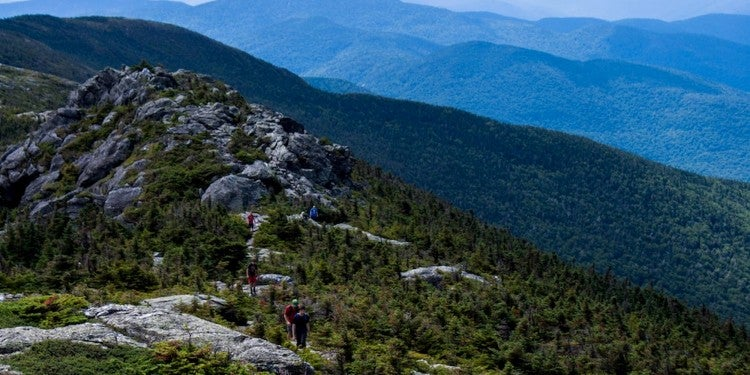 Hikers walking along the rocky ridge of Mt. Mansfield.