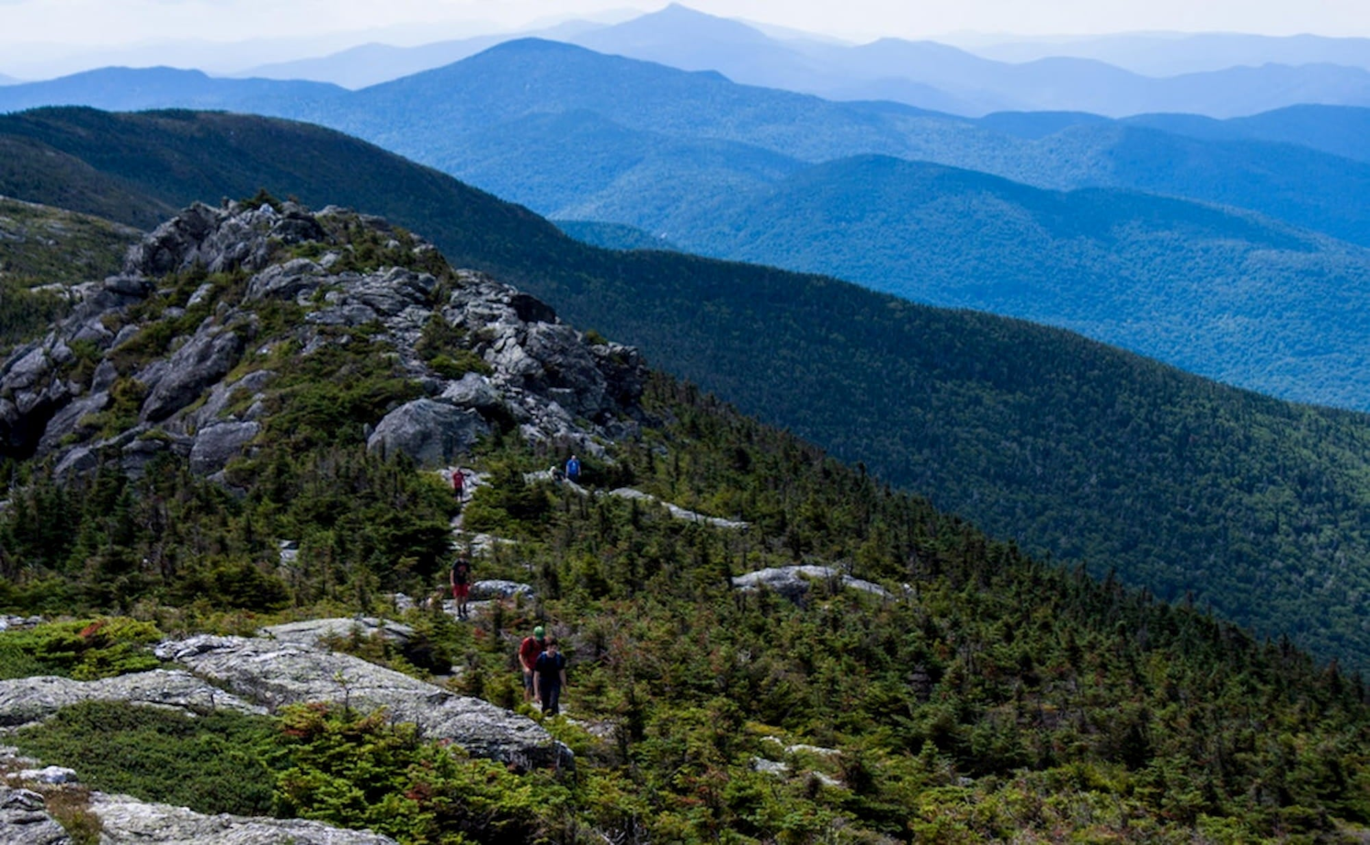Hikers walking along the rocky ridge of Mt. Mansfield.