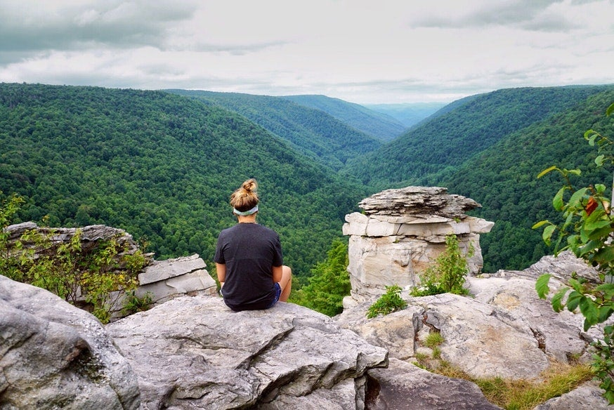 female hiker rests on rocky overlook at West Virginia's Blackwater Falls State Park, photo from a camper on The Dyrt