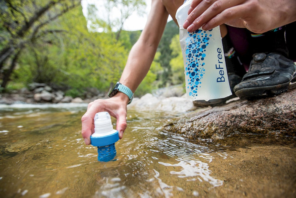 a woman holding a filter up to a river