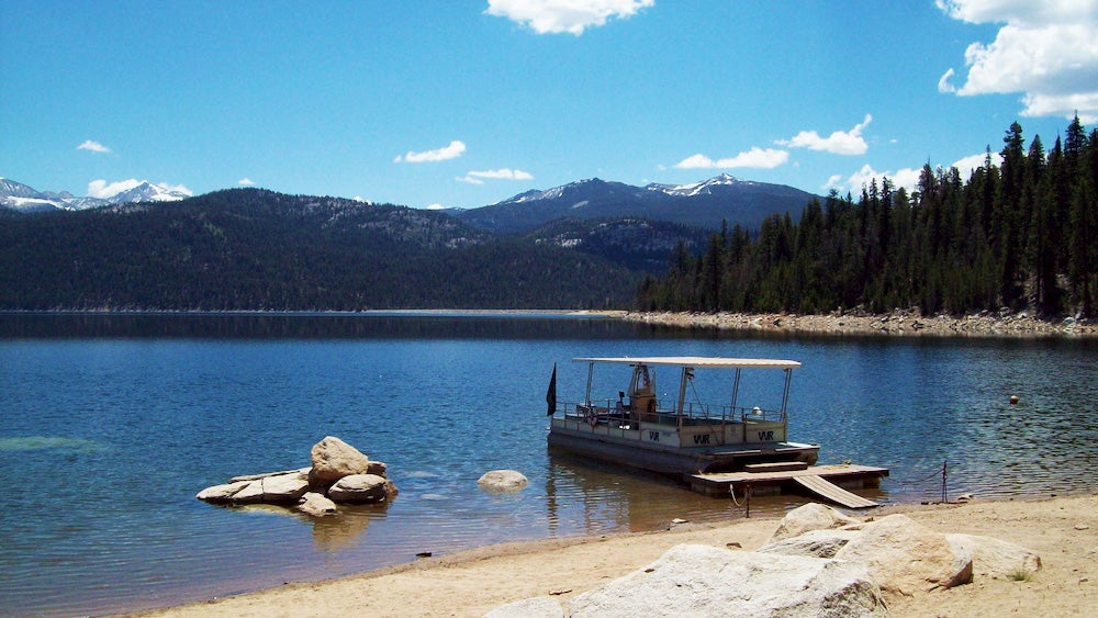 Boat in lake along John Muir Trail with mountain in background