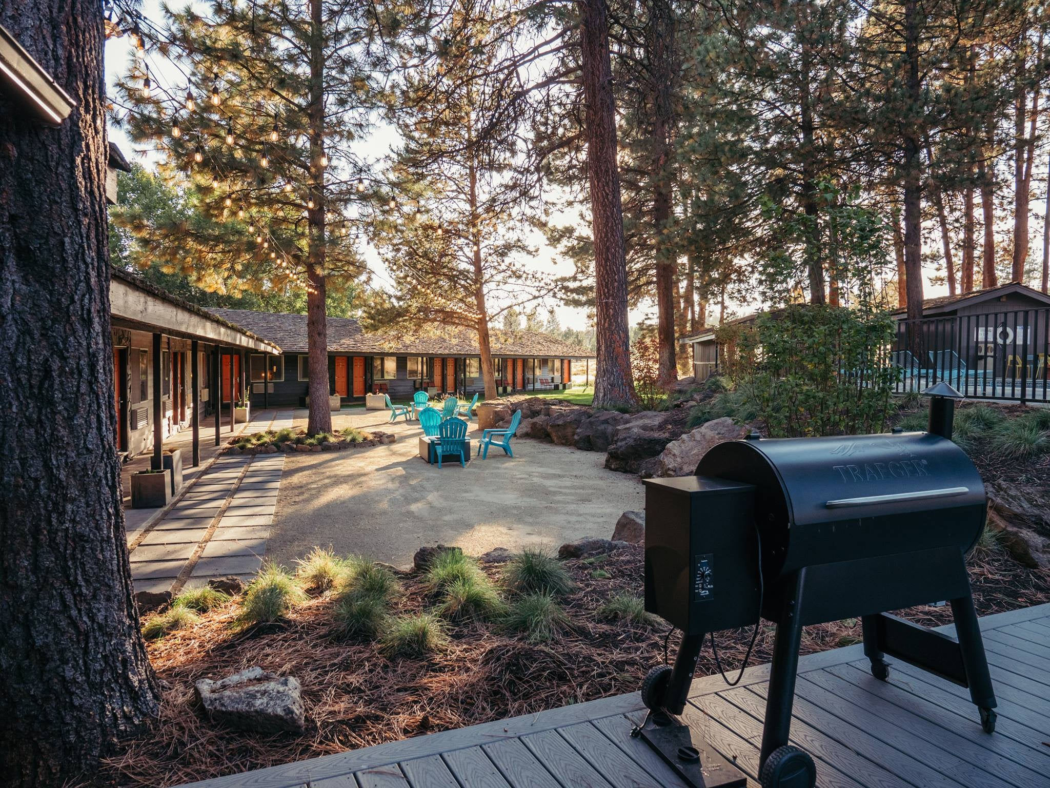 a loge hotel deck with a grill in the woods