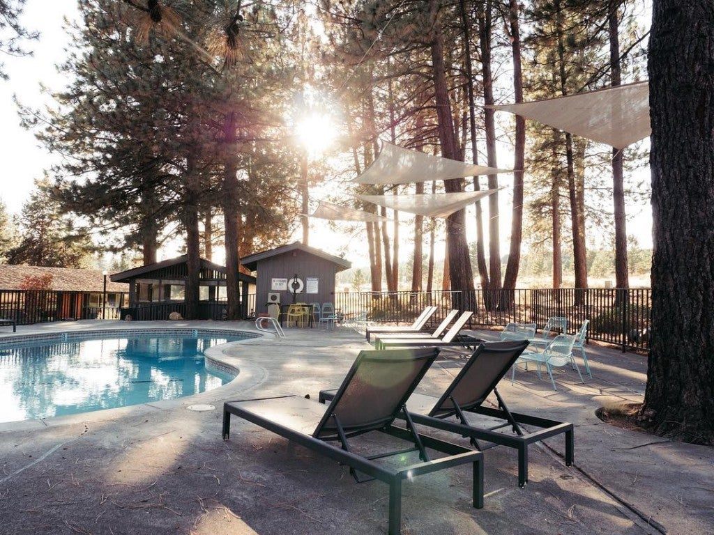 a pool in the woods with chairs and a deck