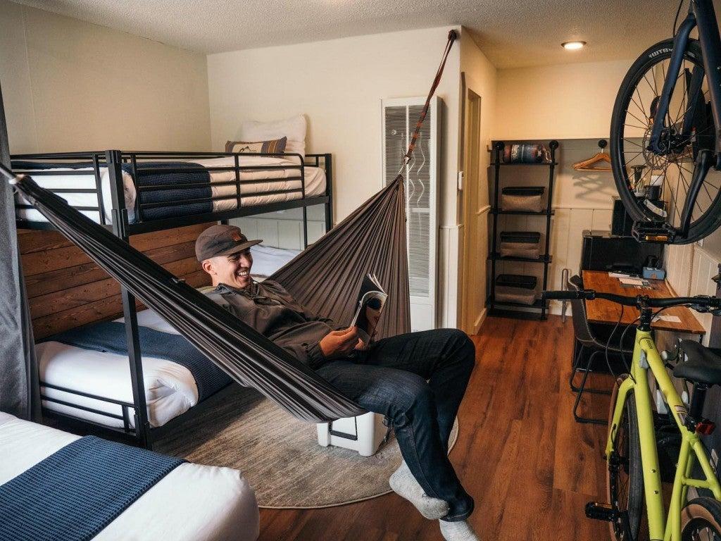 a man sitting in a hammock in a hotel room