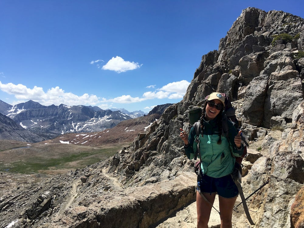 Girl smiling on top of mountain along John Muir Trail