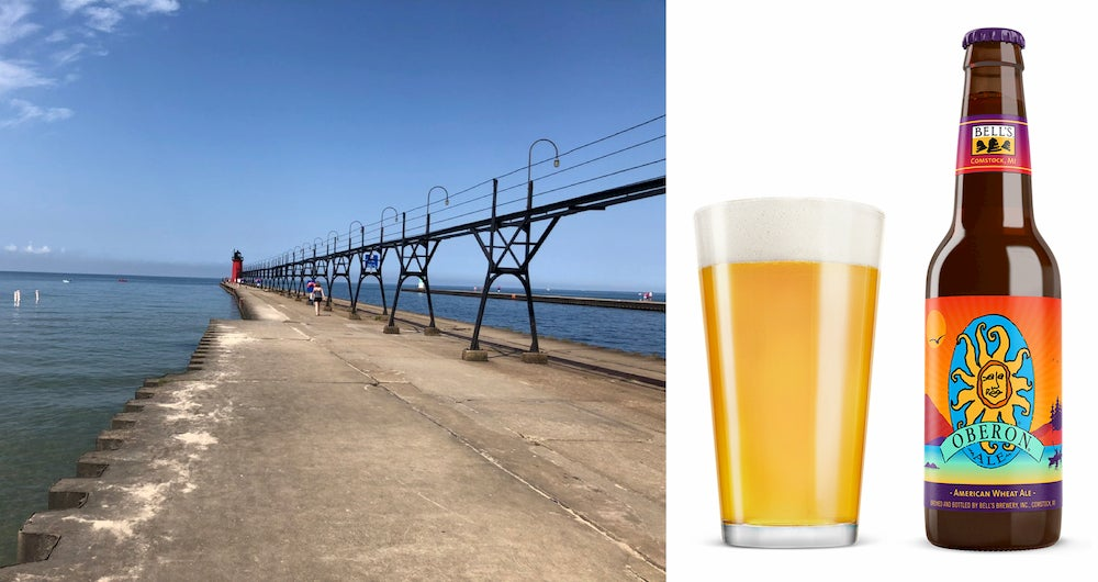 a pier with a lighthouse in michigan next to a glass and bottle of beer