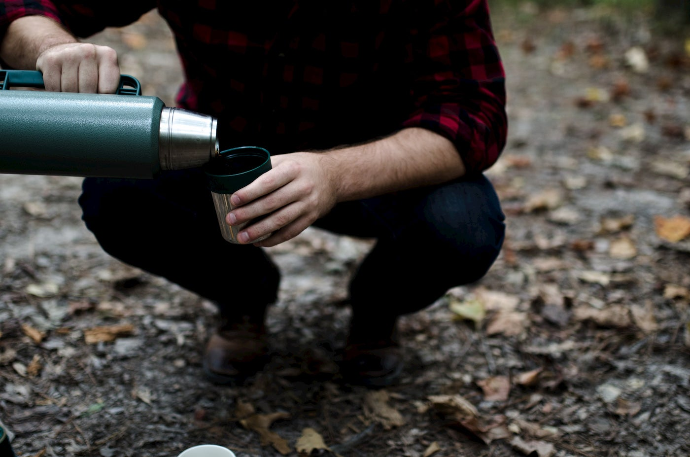 Person pouring coffee from a thermos outdoors.