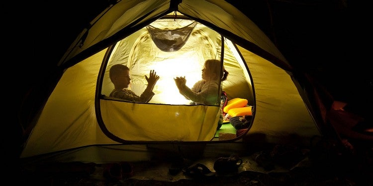 two kids sitting in a glowing tent at night