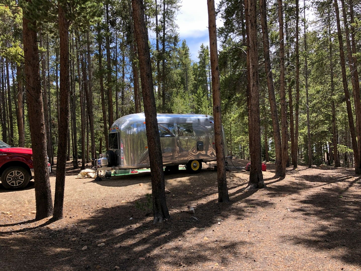 Airstream trailer parked in the woods.