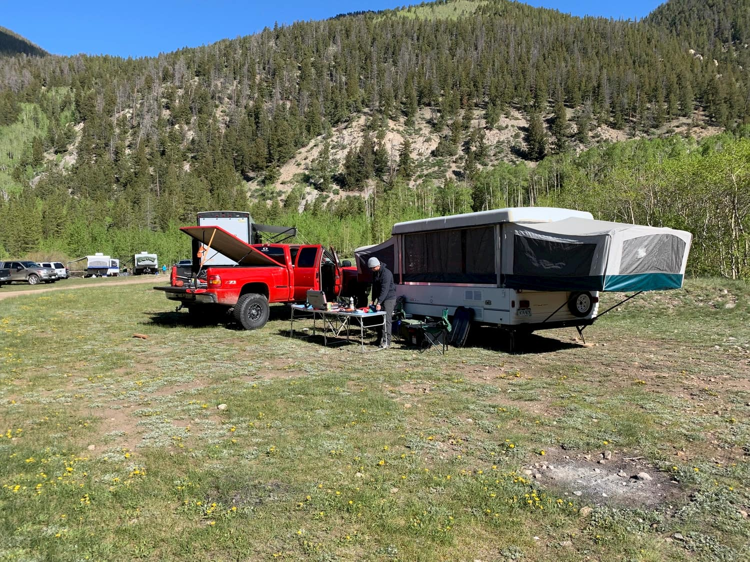 Person cooking at campsite beside pickup truck and pop-up camper.