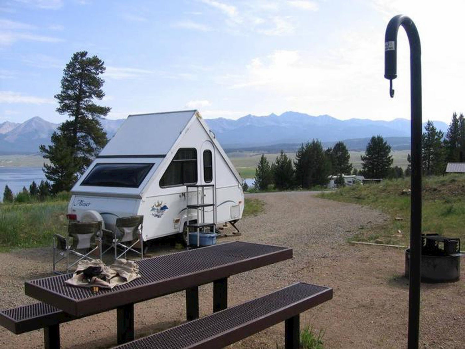 tow camper trailer parked at lakeside campsite with mountains in the background.