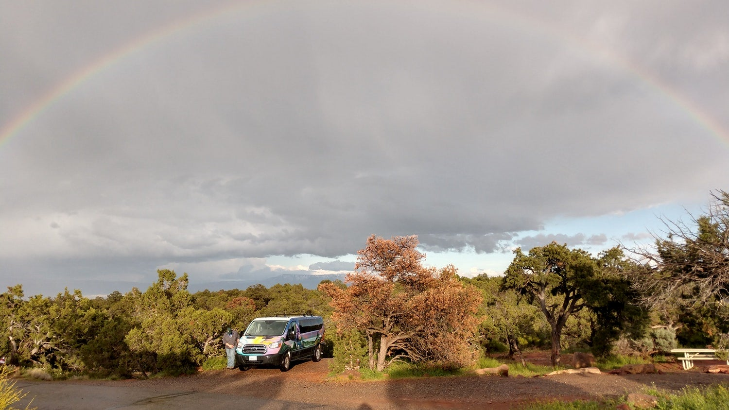 Van parked in sunny campsite with rainbow arch above it.