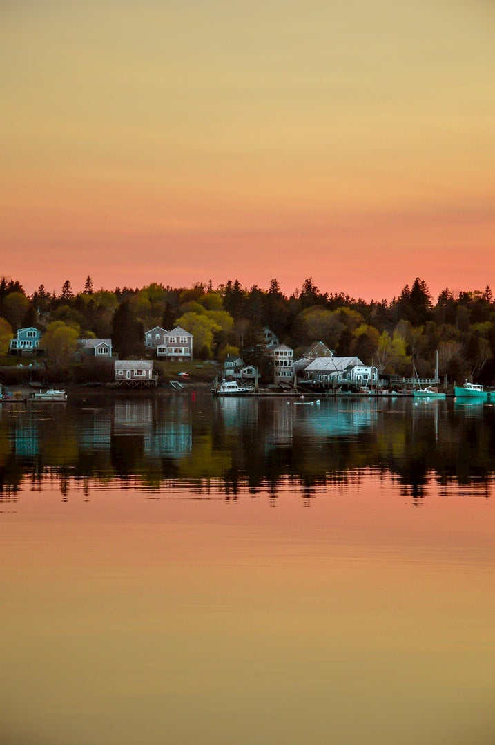 Reflection of the sunset and coastal homes in the ocean below.