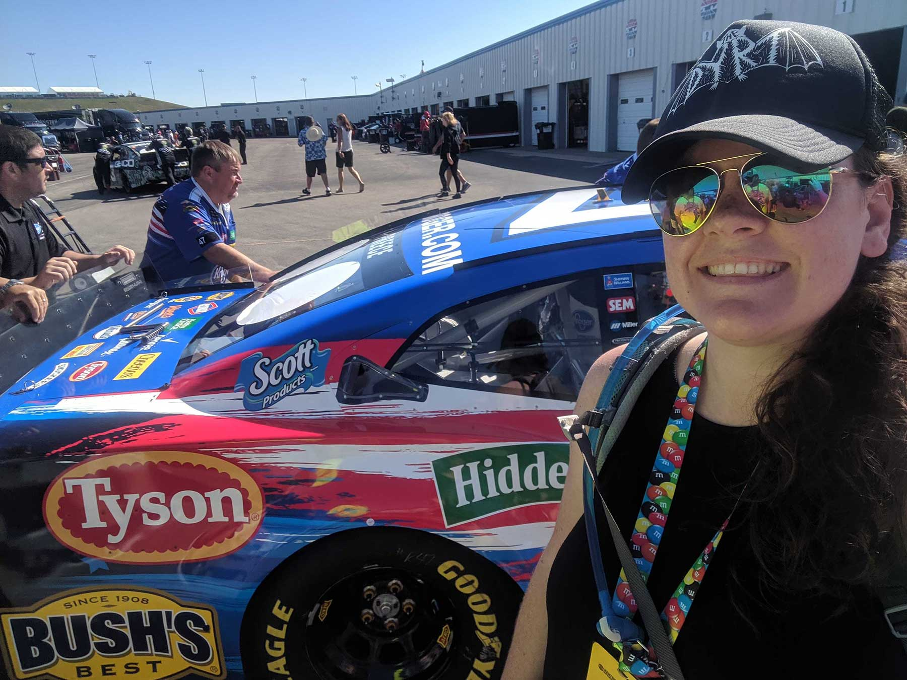 Writer with sunglasses and black baseball cap poses in front of Nascar car.
