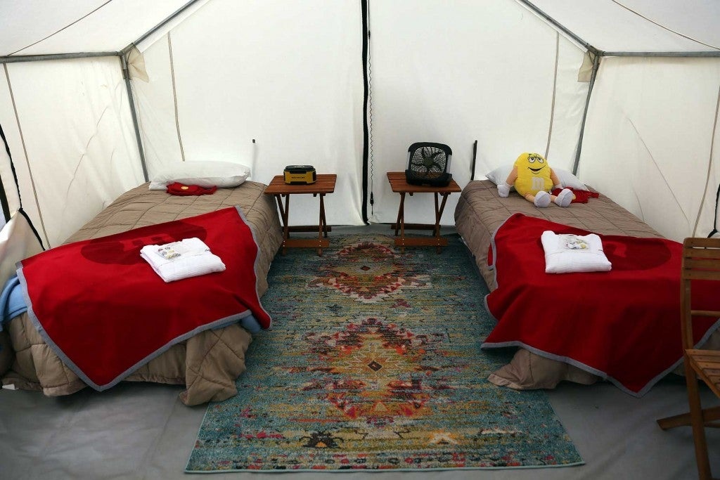 two beds in a glamping tent in a nascar track