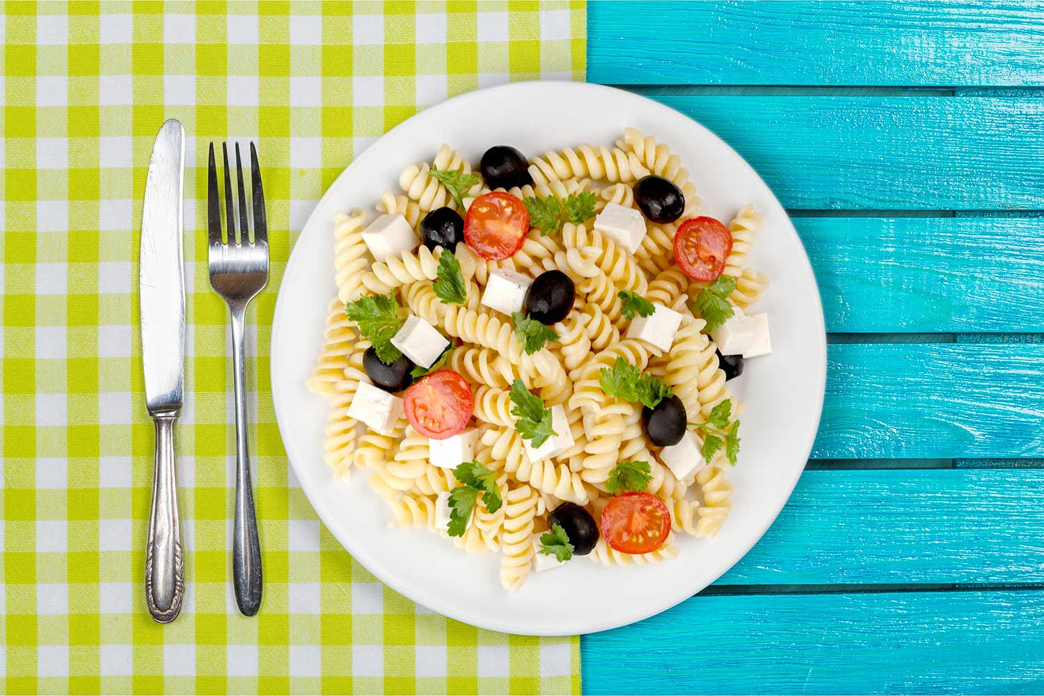 pasta salad on a blue and lime green picnic table