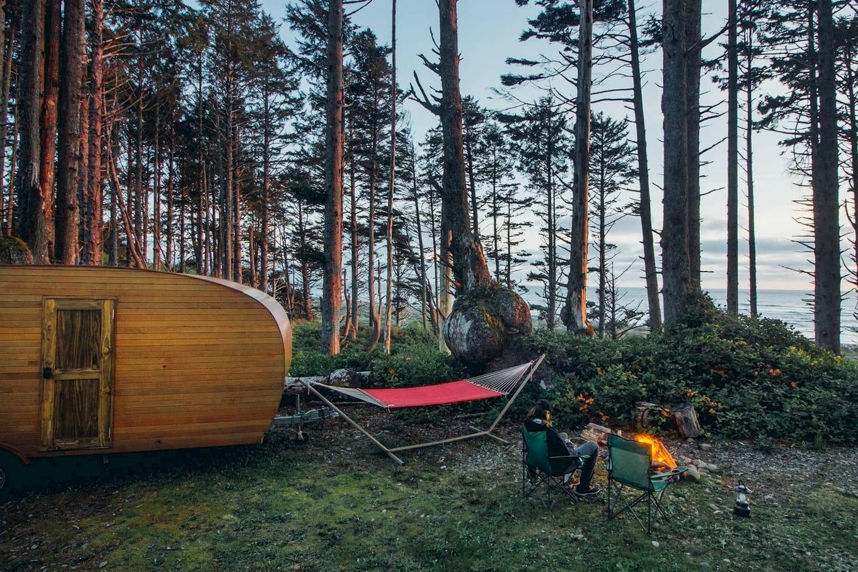 Wood paneled camper, hammock, and campfire on the Washington coast.