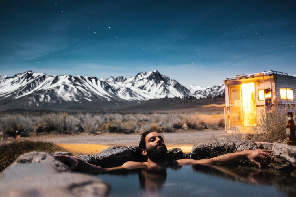 Bearded man lounging in hot springs beside camper in a mountain landscape.