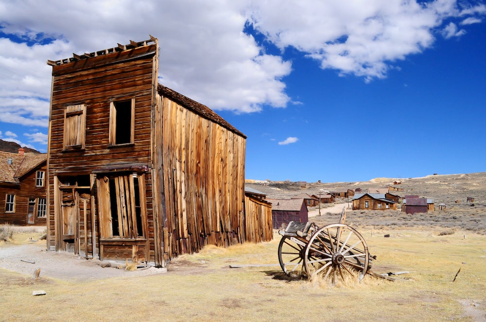 Old abandoned building with carriage and blue sky in background