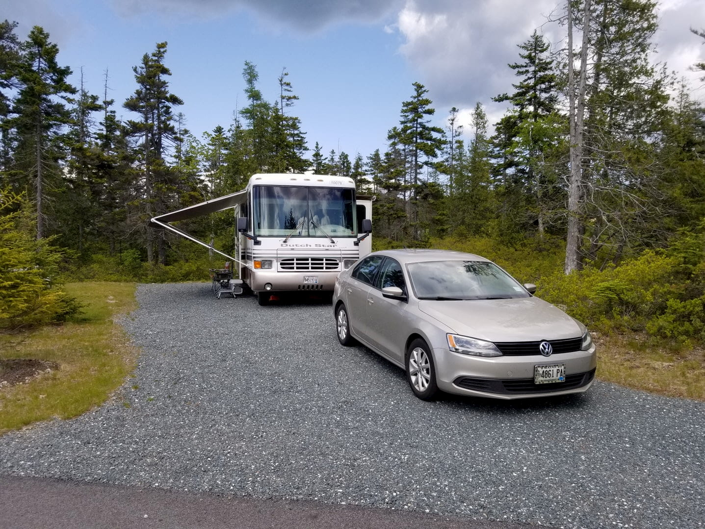R.V. and car parked in gravel campsite beside pine trees.
