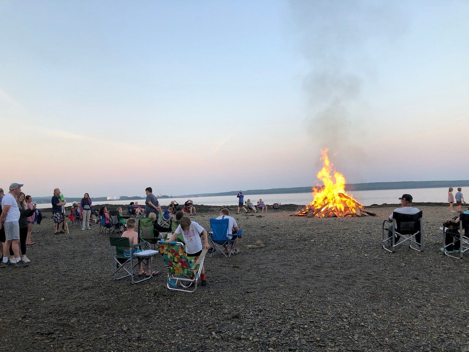 Beach bonfire surrounded by campers in beach chairs.