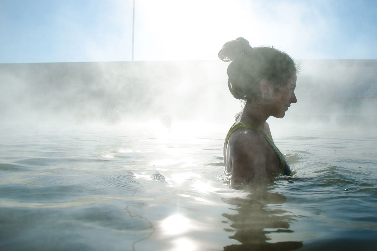 a woman bathes in the mists of a hot spring in california