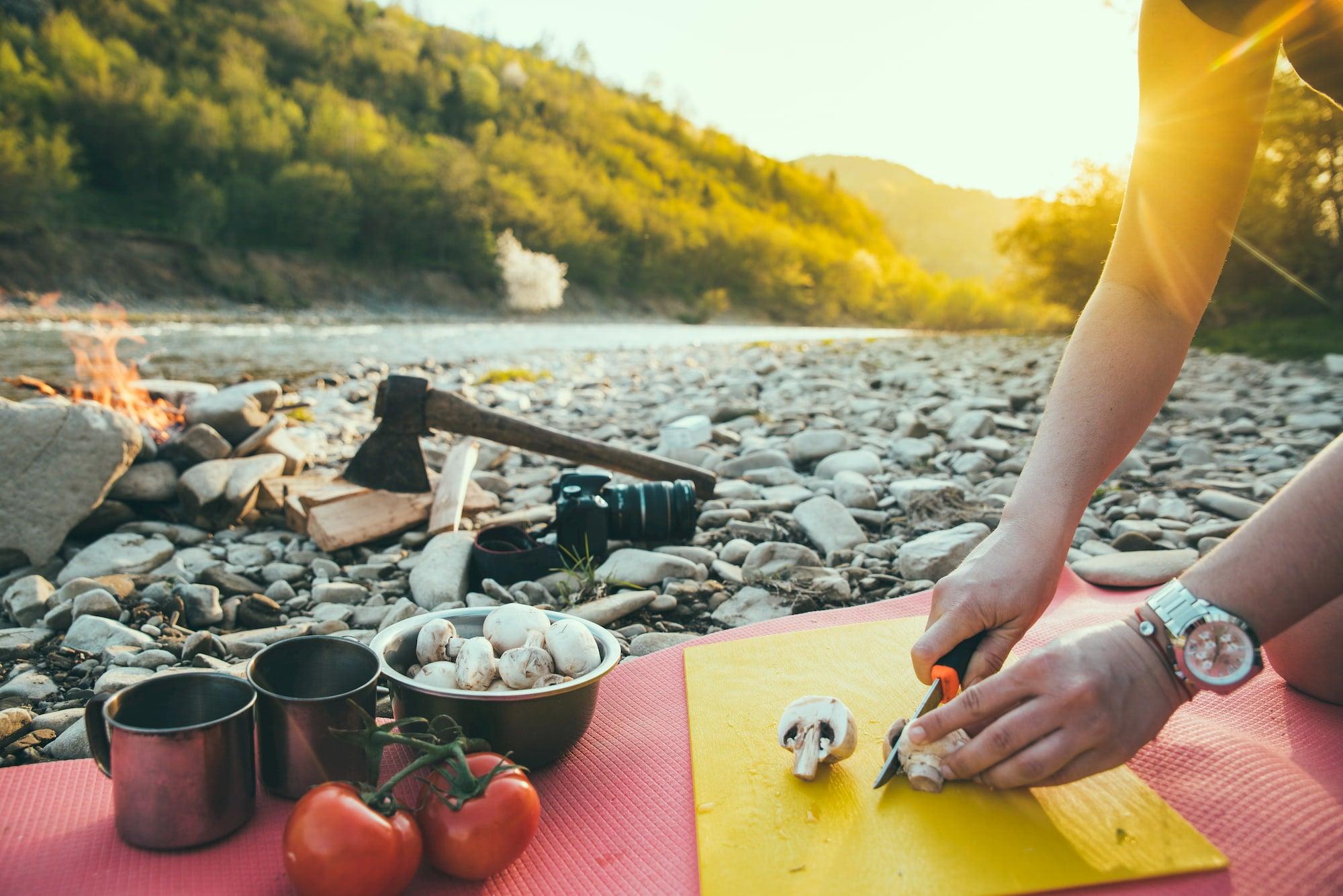 Camper cutting mushrooms on a cutting board beside campfire.